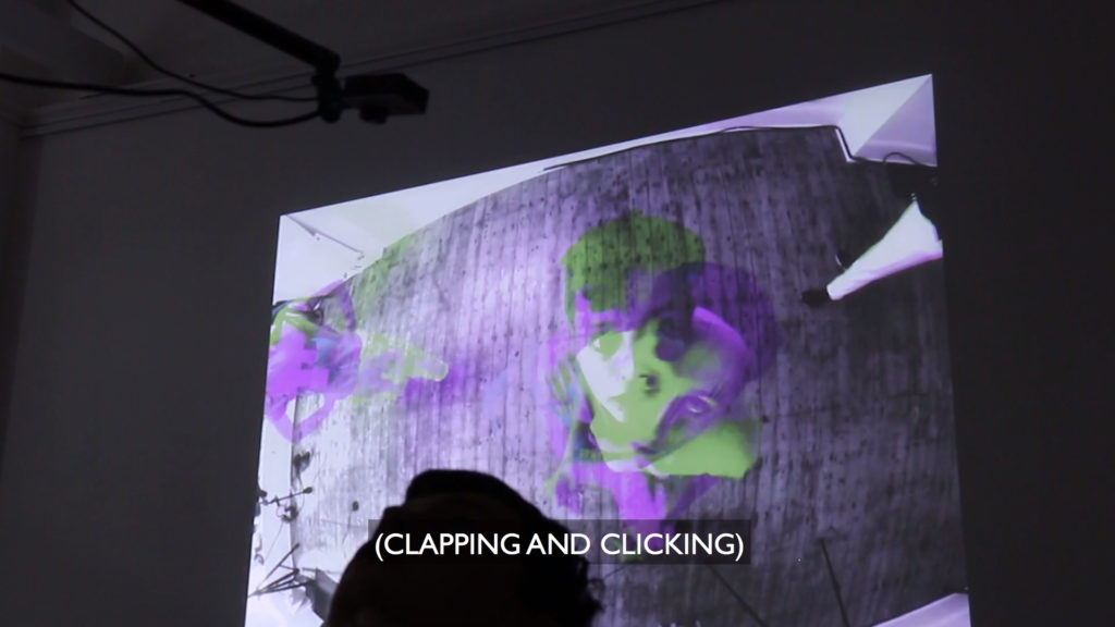 "colour photo of projection on wall of dark room, projection is indistinct green and purple image of three people from above, only one woman's face seen looking up, text '(CLACKING AND CLICKING)"" at bottom of photo"