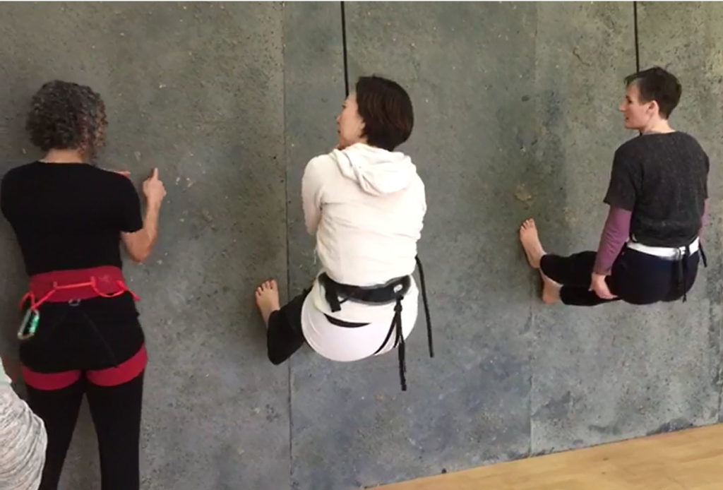 colour photo of three women facing a grey concrete wall, Chisato in the middle and a woman on the right are suspended by ropes, in a sitting position with their feet against the wall, another woman stands on the left wearing a harness, signing