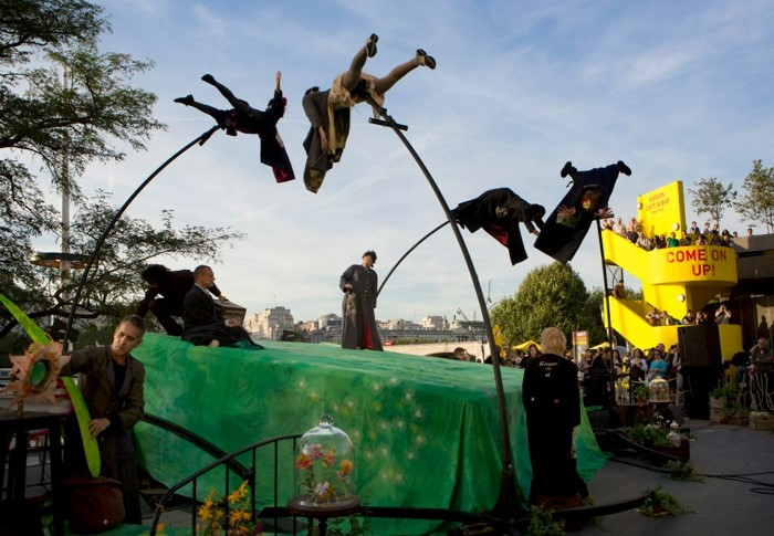 colour photo of outdoor performance, four people above a green sloping stage on top of bending poles all bent over, or in flying or reaching postures, three with feet extended, three people are on the stage, audience are on the ground and on a free-standing yellow staircase, sky is blue