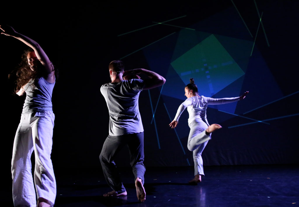 colour photo of three dancers, woman on left facing forward, left arm extended above her head, in middle back view of man, to right back view of woman with arms extended behind and left leg kicking behind