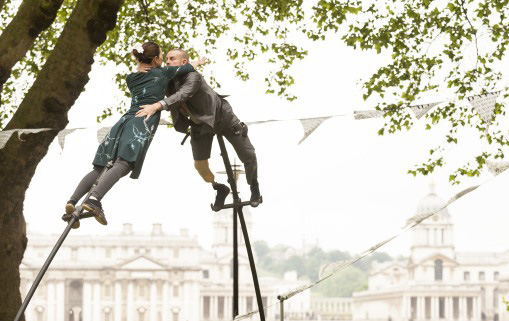 colour photo, man and woman on top of poles, leaning in towards each other with arms around each other, a large tree is behind them, and in the background white historic Greenwich buildings, and white sky