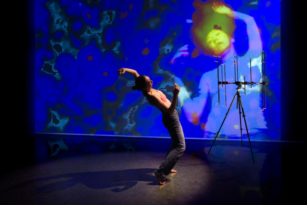 colour photo of side view of female performer in pink vest top, leaning and curving her body backwards, with right hand held in front, left arm held up behind, abstract blue, red black projection behind, with semi-transparent female figure facing forwards in same pose
