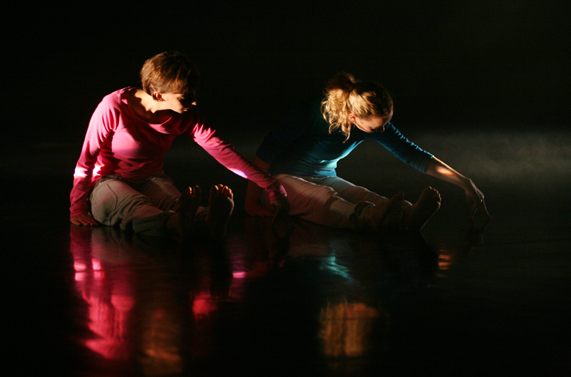 colour photo of two female dancers sitting and reflected in black floor, black background, bare feet extended in front, leaning forward, left arms extended