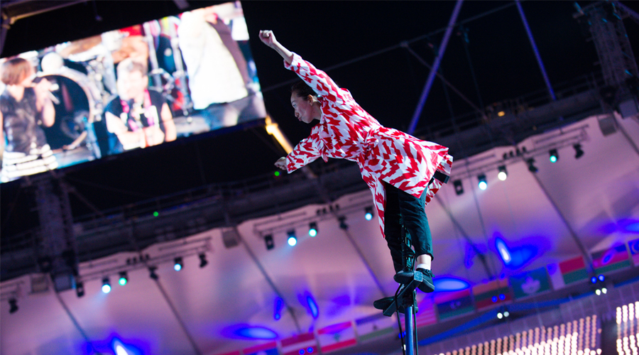 colour photo of Chisato on top of a pole, bending forward with arms extended in fists, wearing red and white dress and dark trousers, in the background stadium roof and lighting, and a screen with an image of out of focus people