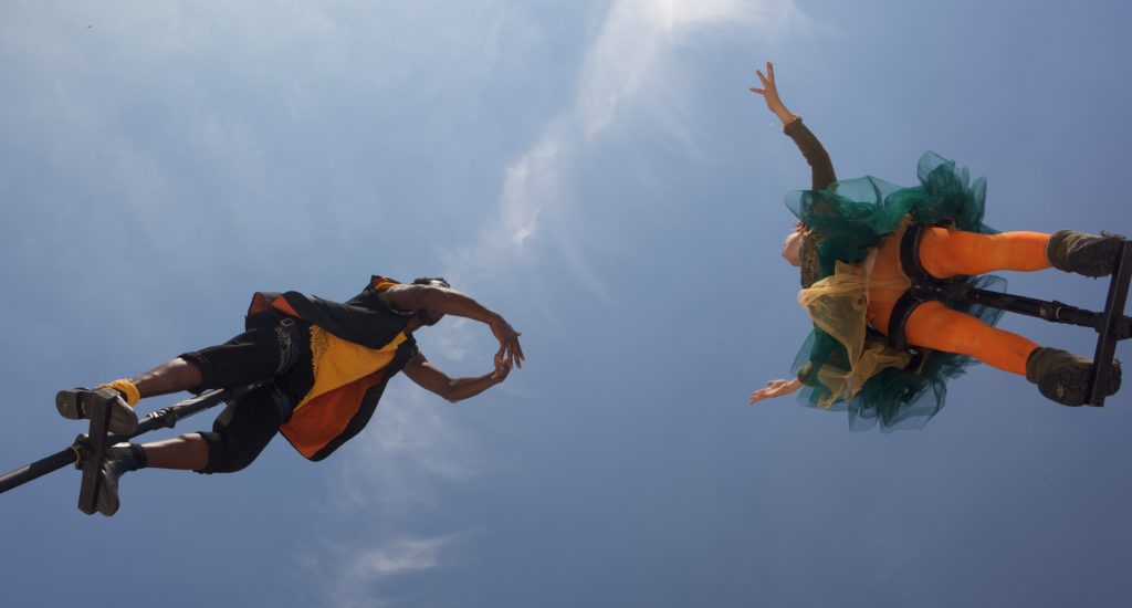 colour photo from below of two people on top of poles against blue sky, faces can not be seen, on the right performer has arms extended to sides, wears orange leggings, green and yellow net garment above, person on left has arms in front with hands touching, wears dark clothes with yellow top and orange jacket lining