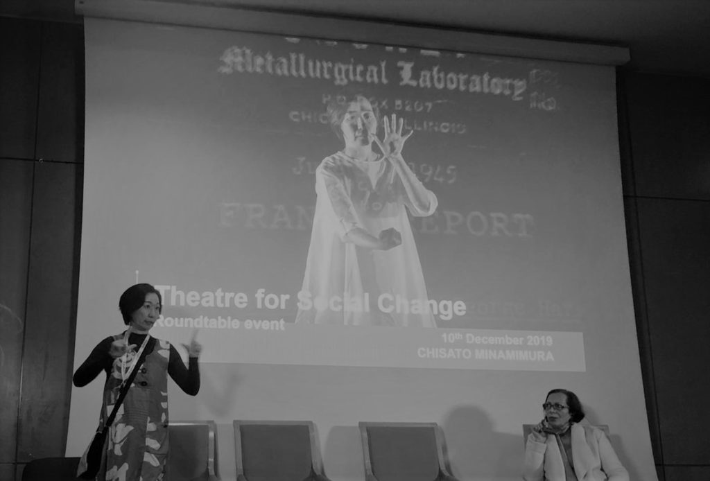 black and white photo of Chisato signing, wearing a patterned dress, standing in front of a row of chairs and one seated woman, in the background a projected image of Chisato performing with text behind her, and overwritten with conference details